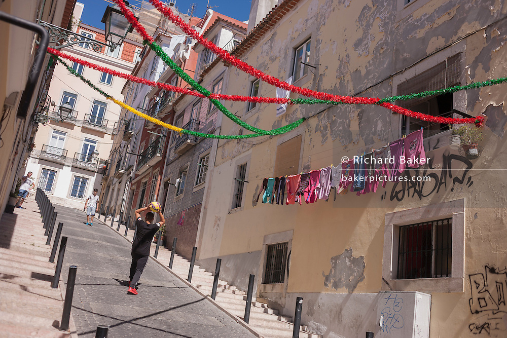 An impromptu kickabout with a ball on a steep street in Bairro Alto, Lisbon, Portugal.
