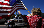Arlene Moyle holds a flag as she waves to fire trucks passing by in a procession escorting the flag draped coffin of California Department of Forestry firefighter Eva Marie Schicke along Main Street in Angels Camp, Calif., Monday, Sept. 20, 2004. Schicke died Sept. 12 while battling a fire in Stanislaus National Forest. Several hundred fire trucks from around the state followed in the procession to the Calaveras County Fairground for the memorial services.