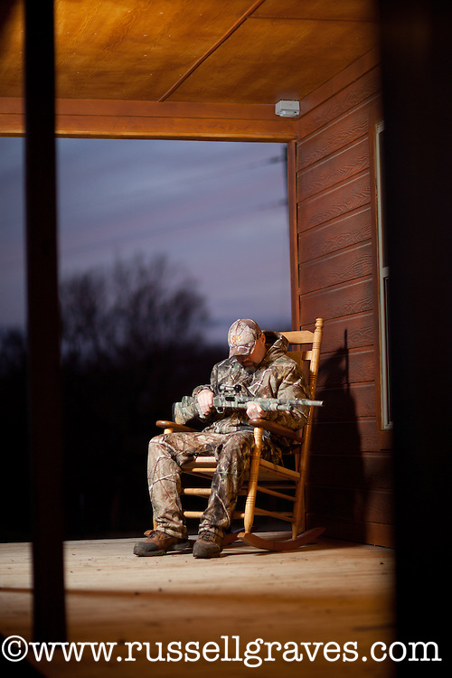 DEER HUNTER ON THE PORCH OF HIS HUNTING CAMP
