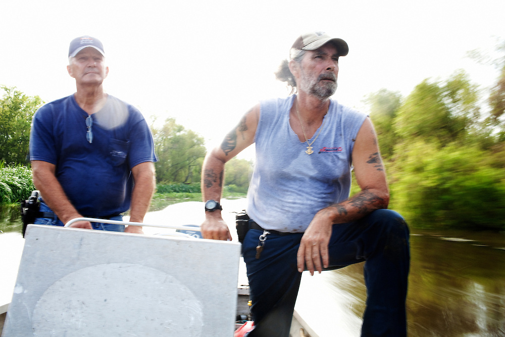 Julius Gaudet, 62, (L) and Rebel (R) glide over the tranquil surface early in the morning as they begin their day hunting for alligators.
