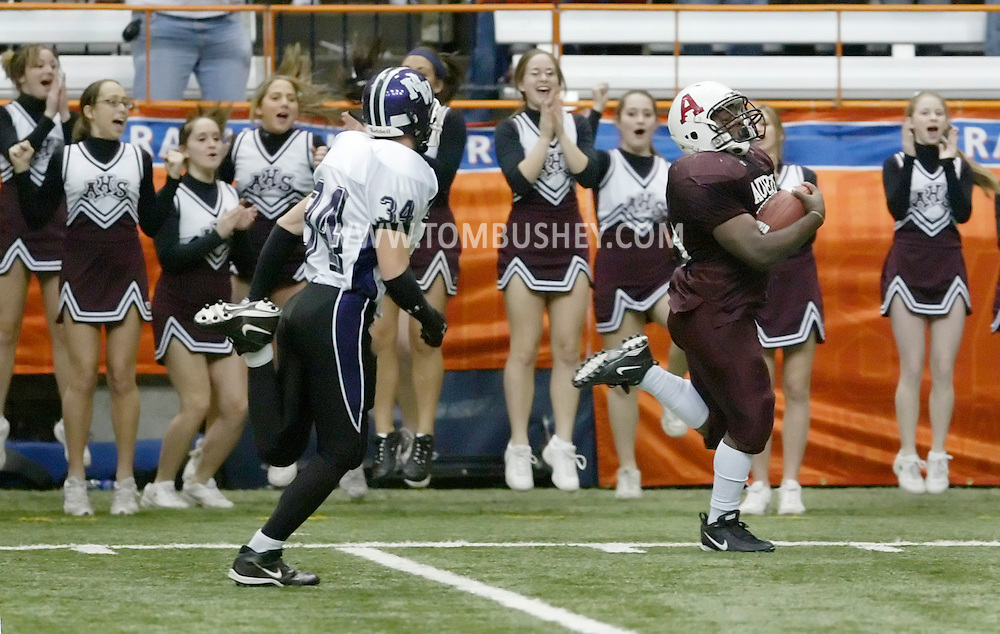 Auburn's John Ravenell, right, heads for the end zone to score on a 50-yard pass reception as Monroe-Woodbury's Keith Coincan trails the play and the Auburn cheerleaders celebrate in the background during the Class AA state championship game at the Carrier Dome in Syracuse on Nov. 25, 2006.