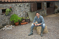 Man sitting on hay bale outside stable portrait