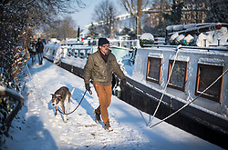 © Licensed to London News Pictures. 28/02/2018. London, UK. A man walks a dog through picturesque scenes at sunrise in Little Venice, West London following heavy snowfall last night. Large parts of the UK are experiencing disruption as 'Storm Emma' hits, following Russian a cold front earlier in the week named 'The Beast From The East'. Photo credit: Ben Cawthra/LNP
