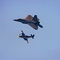 A Lockheed F-22A Raptor flies in formation with a World War II era Lockheed P-51 Mustang during the 2012 Bethpage Air Show at Jones Beach. The two were flying together as part of a Heritage Flight display which pairs vintage fighter aircraft with their current day counterparts.