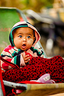 a burmese baby looking surprised in his stroller, kalaw, myanmar