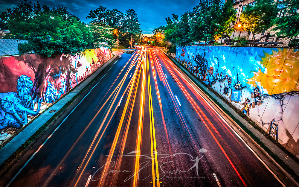 Traffic travels past colorful murals along Chamblee-Dunwoody Road, June 1, 2014, in Chamblee, Georgia. The 100-by-20 foot murals were painted in 2008 by local graffiti artist Amir Totem for Chamblee's centennial celebration. (Photo by Carmen K. Sisson/Cloudybright)
