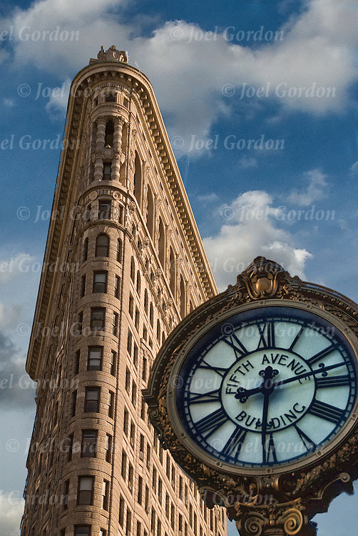 Fifth Avenue Clock in foreground looking up at the  Flatiron Building at 175 Fifth Avenue New York City and is considered to be a groundbreaking skyscraper.<br /> <br /> Upon completion in 1902 it was one of the tallest buildings in the city and the only skyscraper north of 14th Street. <br /> <br /> The building sits on a triangular island block formed by Fifth Avenue, Broadway and East 22nd Street, with 23rd Street grazing the triangle's northern (uptown) peak. It anchors the south (downtown) end of Madison Square, and the north (uptown) end of the Ladies' Mile Historic District.