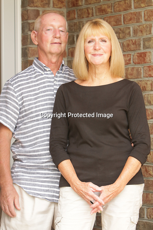 Dan and Sallye Neizmik pose for a portrait at their home in Leland. (Jason A. Frizzelle)