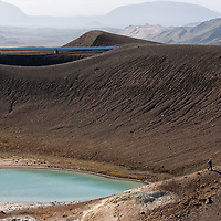 Tourists walking along the small turquoise crater which is located just next to the Stóra-Víti crater.