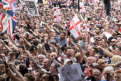 © Licensed to London News Pictures. 09/06/2018. London, UK. supporters of EDL founder Tommy Robinson ( real name Stephen Yaxley-Lennon ) on Whitehall chanting at police during a demonstration in Westminster following Robinson's conviction for Contempt of Court . Robinson was already serving a suspended sentence for Contempt of Court over a similar incident , when he was convicted on Friday 25th May 2018 . Photo credit: Joel Goodman/LNP