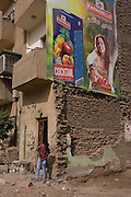 A local man sweeps away dust beneath a poster for healthy living with wasteground dereliction in Luxor, Nile Valley, Egypt.