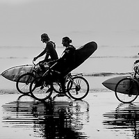 Surfers on the beach at Tofino, BC, pedalling to the next great spot.