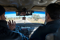 Taxi driver and passenger on rural road passing through olive trees in northern Syria, en route from the Turkish border at Bab al-Hawa to Atmeh (January 2013)