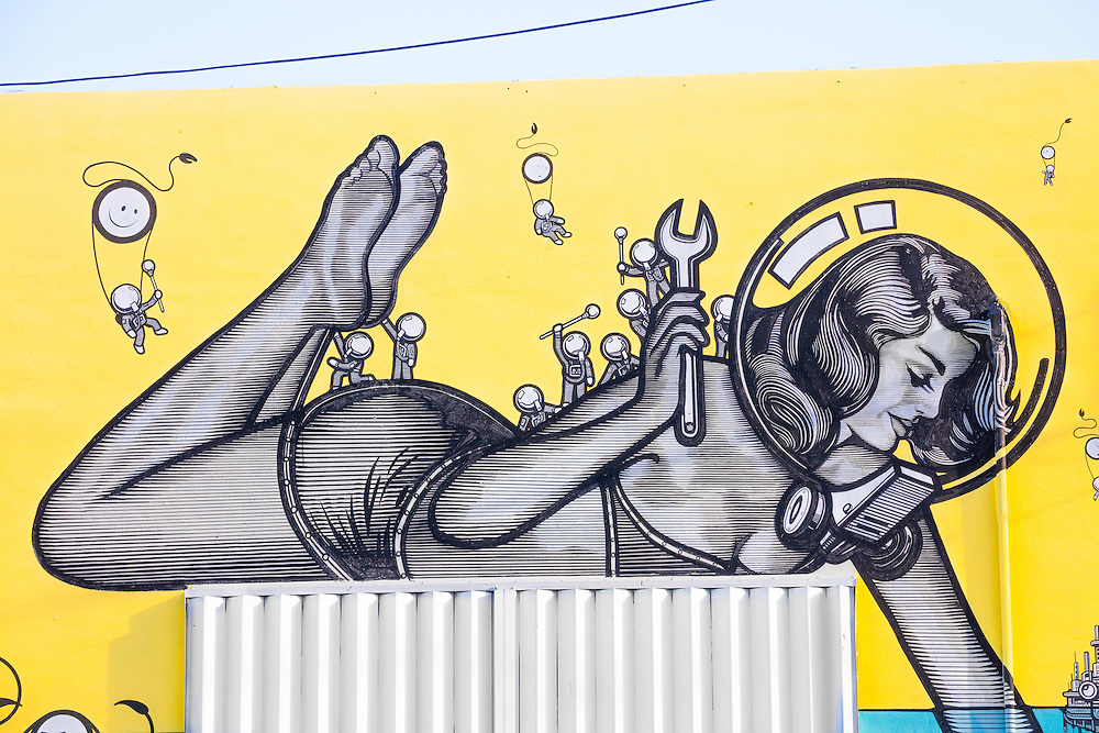 A giant pin-up wears a bubble-like diving helmet and a two-piece bathing suit in a whimsical, 1950s-ish, science fiction-like mural in Miami's Wynwood arts district