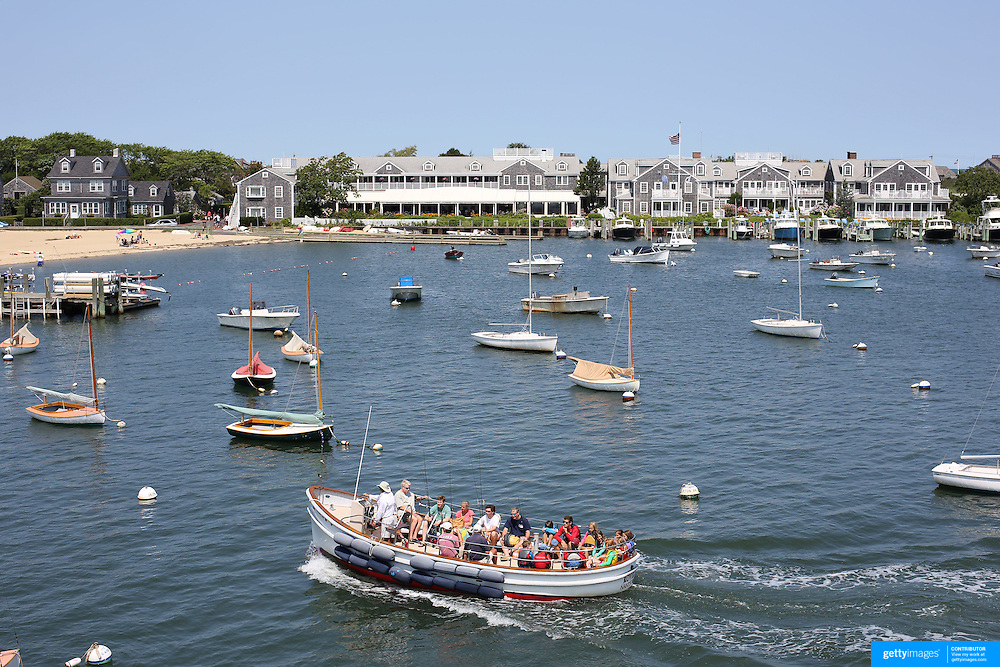 A fishing trip returns to the harbor passing sail boats moored in Nantucket Harbor, Nantucket Island, Massachusetts, USA. Photo Tim Clayton