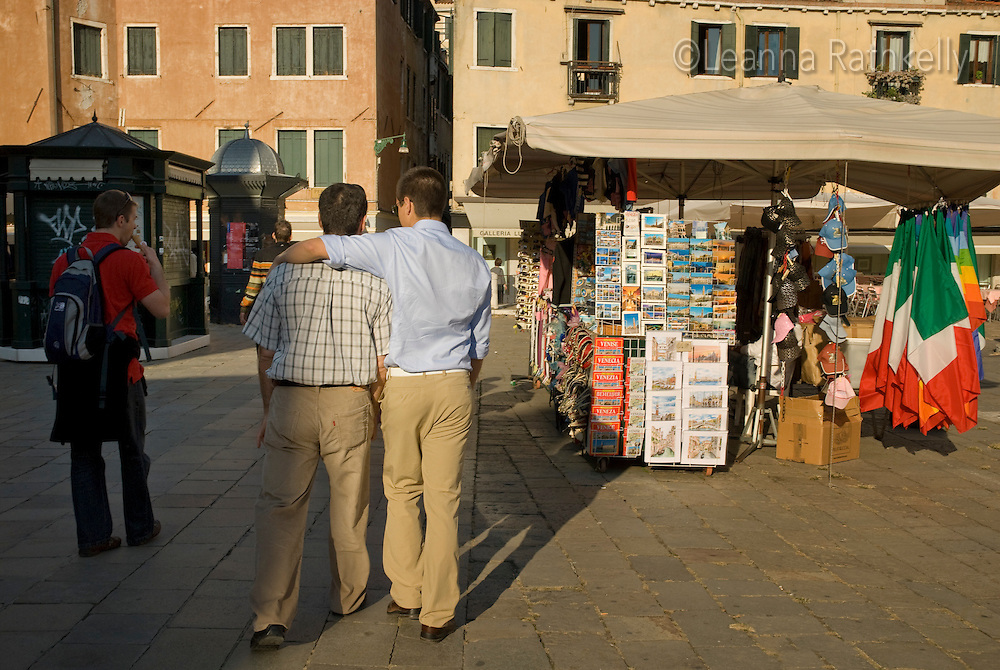 Teenage son hugs his Dad as they walk by a tourist stand in Venice, Italy.