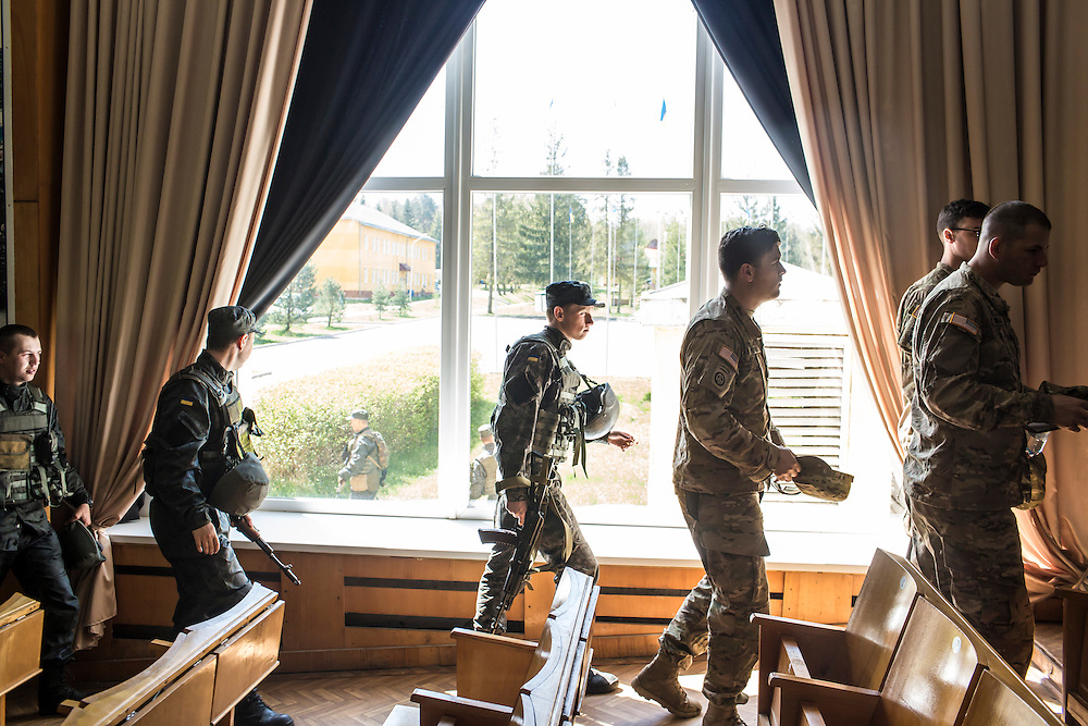YAVORIV, UKRAINE - APRIL 30, 2015: Ukrainian soldiers follow American soldiers from the U.S. Army's 173rd Airborne Brigade out of an auditorium after a debrief of a military training exercise as part of Operation Fearless Guardian at the Yavoriv training center near Yavoriv, Ukraine. Around 300 American soldiers are training an equivalent number of Ukrainians during each of three eight-week programs to improve their ability to combat Russian-backed rebels in the country's east. CREDIT: Brendan Hoffman for The New York Times