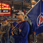 Chicago Cubs fan listens to game 7 on a radio outside Wrigley Field.  Cubs won the World Series against the Cleveland Indians in 7 games.<br />