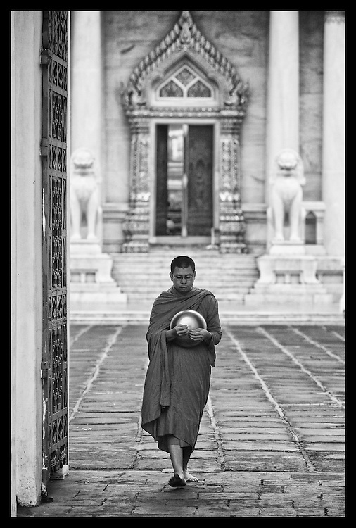 A Thai Buddhist Monks walks his morning rounds at Wat Bencha in Bangkok, Thailand.