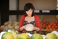 Young woman selecting melon in food market