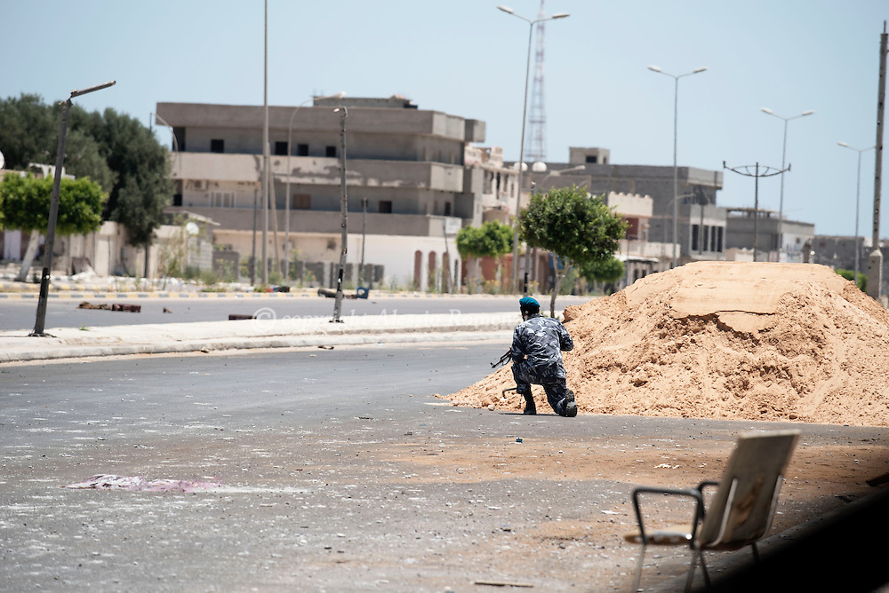 Libya: A Libya's Government of National Accord's (GNA) fighter ducks behind a sand berm on the western frontline with ISIS in Sirte, Alessio Romenzi