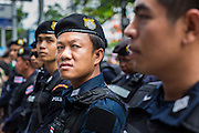 24 MAY 2014 - BANGKOK, THAILAND: Thai riot police gather on Phahon Yothin Street in Bangkok while anti-coup protestors are nearby. There were several marches in different parts of Bangkok to protest the coup that unseated the popularly elected government. Soldiers and police confronted protestors and made several arrests but most of the protests were peaceful. The military junta also announced that firing of several police commanders and dissolution of the Thai Senate. The junta also changed its name from National Peace and Order Maintaining Council (NPOMC) to the National Council for Peace and Order (NCPO).   PHOTO BY JACK KURTZ