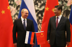 epa04482559 Russian and Chinese national flags are seen on the table with Russian President Vladimir Putin (L) and his Chinese counterpart Xi Jinping in the background during a signing ceremony at the Diaoyutai State Guesthouse, on the sidelines of the Asia-Pacific Economic Cooperation (APEC) 2014 Summit, in Beijing, China, 09 November 2014. The APEC 2014 Summit and related meetings will be held in Beijing from 05 to 11 November, gathering leaders of 21 member economies.  EPA/HOW HWEE YOUNG / POOL