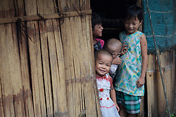 A group of kids stick out of their house's door in the Je Yang refugee camp near to Laiza village close to the China border, Myanmar on August 1, 2012. This is the biggest IDP camp in Laiza with 6847 refugees according to KIO (Kachin Independence Organization) on 24 July, 2012, also ccording to the same sources around 50000 Kachin people live as refugees in those camps.