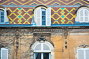 Traditional polychrome roof tiles and window shutters on a period building in Dijon in the Burgundy region of France
