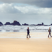 3 young women walking on the beach in Ecola State Park, Oregon Coast.
