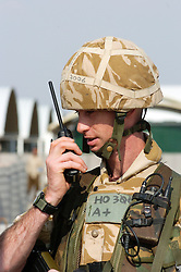 A British soldier, from the Muliti National Division (MND SE) speaks on a walkie talkie two way radio while manning a security gate at Allenby Lines on Basra Air Station during Operation Telic in March 2005