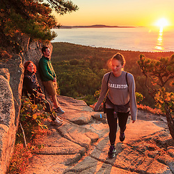 "Hikers at sunrise  on ""The Beehive"" in fall in Maine's Acadia National Park."