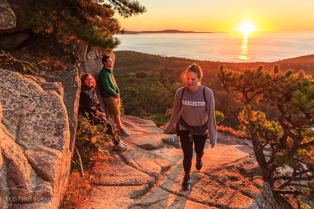 """Hikers at sunrise  on """"The Beehive"""" in fall in Maine's Acadia National Park."""
