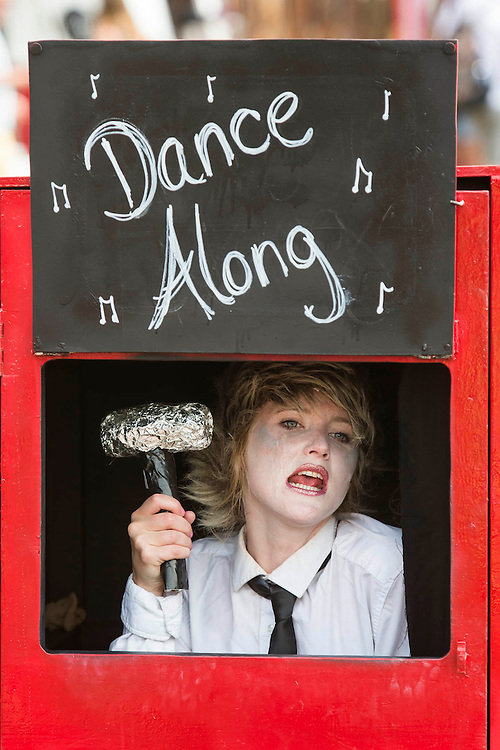 Performers mime to pop songs in smallred boxes. The 2015 Glastonbury Festival, Worthy Farm, Glastonbury.