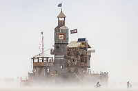 The Folly<br /> by: Dave Keane & The Folly Builders<br /> from: San Francisco, CA<br /> year: 2019<br /> <br /> The Folly represents an imaginary shantytown of funky climbable towers and old western storefronts, cobbled together from salvaged and reclaimed lumber from original San Francisco Victorians to be reborn in the desert, affording shelter, entertainment and perspective to the community.<br /> <br /> URL: www.thefollybrc.com<br /> Contact: info@thefollybrc.com<br /> <br /> https://burningman.org/event/brc/2019-art-installations/?yyyy=&artType=H#a2I0V000001AVkAUAW