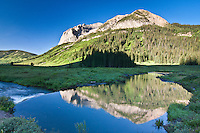 Reflections of 12625 ft. Gothic Mountain  in the East River along the Gothic road.  Colorado.