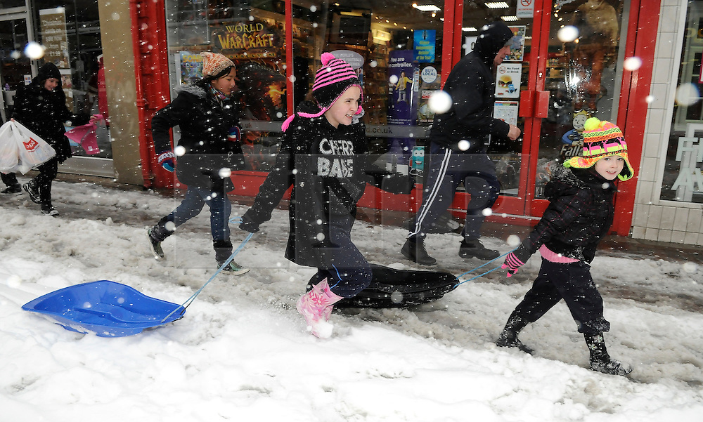 © under license to London News Pictures. 1.12.2010 Snow chaos in Orpington in Kent. Children with sledges running down Orpington High Street. . Picture credit should read Grant Falvey/London News Pictures