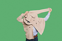 Man struggling to wear jacket over colored background