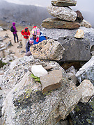 A cairn of small rocks brought up the trail, along with coca leaves, at Salkantay Pass, giving thanks for making it to this point, along the Camino Salkantay,  near Soraypampa, Peru.