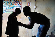 """Sorie Koroma helps his son Noah, 9 years old get dressed for school at their home in the suburb of Mount Aureol, Freetown, Sierra Leone on May 30, 2017. Sorie is a single father of two children, Noah 9 and Zainab 20 months. His wife died in December 2015 few days after giving birth to their younger child, Zainab. Sorie was struggling to take care of baby Zainab so she asked her grandmother to take her in. Sorie tries to keep Noah busy to ensure he doesn't get into trouble """"Because of the kind of job I have at the moment, I don't come home very early so I pay for after school lessons to keep him busy."""" He is a taxi driver but he doesn't work on Sundays because he wants to spend time with Noah and help him with his homework."""