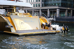 © Licensed to London News Pictures. 17/09/2019. London, UK. Crew secure gold wrapped, 175 feet long superyacht, Bellami.com at her mooring in East India Dock. It took 13 days and 600sqm of gold chrome vinyl wrap to cover the superyacht formally known as 'Kinta' at the Port of Viareggio in Italy this year and is the largest chrome yacht wrap done fully in the water and possibly the largest chrome wrap ever. As Bellami.com arrived, it was noticed that some of the chrome wrap was already damaged and missing. Photo credit: Vickie Flores/LNP