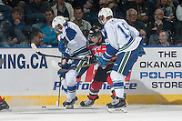 KELOWNA, CANADA - OCTOBER 7: Nick Merkley #10 of Kelowna Rockets digs for the puck against Brett Lernout #4 and Jake DeBrusk #19 of Swift Current Broncos on October 7, 2014 at Prospera Place in Kelowna, British Columbia, Canada.  (Photo by Marissa Baecker/Getty Images)  *** Local Caption *** Brett Lernout; Jake DeBrusk; Nick Merkley;