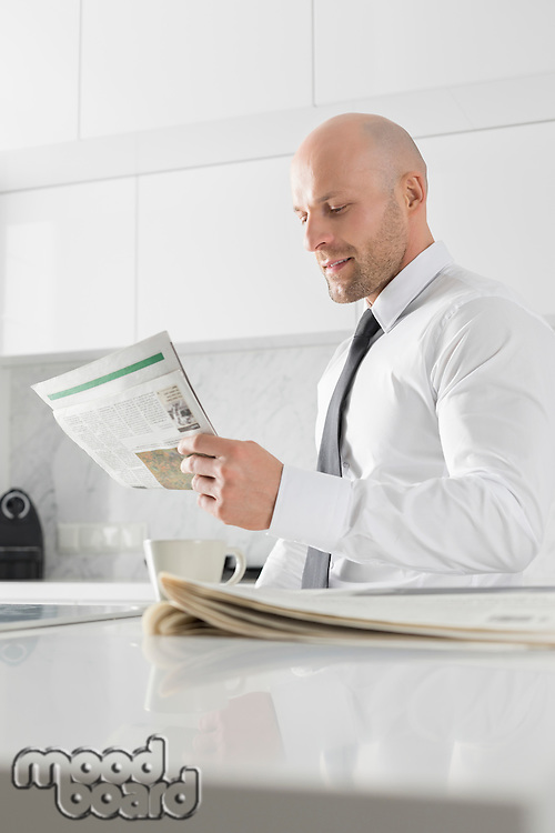 Mid adult businessman reading newspaper at kitchen counter