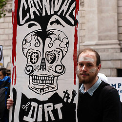 London, UK - 15 June 2012: a man holds a banner reading 'Carnival of Dirt'. More than 30 activist groups from London and around the world have come together to highlight the illicit deeds of mining and extraction companies.