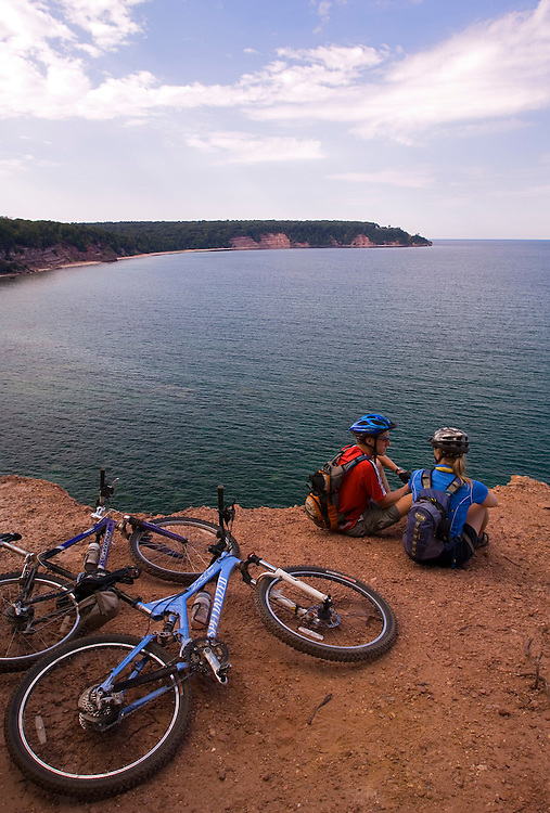 Mountain bikers stop at a cliff overlook of North Bay on Grand Island National Recreation Area in Munising Michigan.