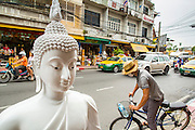 """12 NOVEMBER 2012 - BANGKOK, THAILAND:   A man bicycles past an unpainted statue of the Buddha on Bamrung Muang Street in Bangkok. Thanon Bamrung Muang (Thanon is Thai for Road or Street) is Bangkok's """"Street of Many Buddhas."""" Like many ancient cities, Bangkok was once a city of artisan's neighborhoods and Bamrung Muang Road, near Bangkok's present day city hall, was once the street where all the country's Buddha statues were made. Now they made in factories on the edge of Bangkok, but Bamrung Muang Road is still where the statues are sold. Once an elephant trail, it was one of the first streets paved in Bangkok. It is the largest center of Buddhist supplies in Thailand. Not just statues but also monk's robes, candles, alms bowls, and pre-configured alms baskets are for sale along both sides of the street.    PHOTO BY JACK KURTZ"""