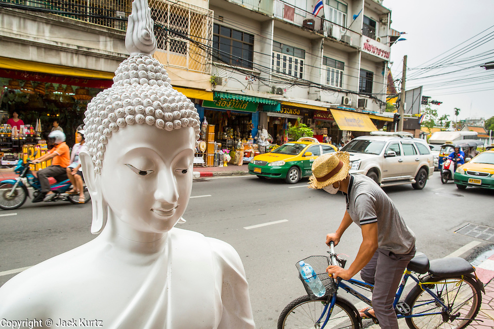 "12 NOVEMBER 2012 - BANGKOK, THAILAND:   A man bicycles past an unpainted statue of the Buddha on Bamrung Muang Street in Bangkok. Thanon Bamrung Muang (Thanon is Thai for Road or Street) is Bangkok's ""Street of Many Buddhas."" Like many ancient cities, Bangkok was once a city of artisan's neighborhoods and Bamrung Muang Road, near Bangkok's present day city hall, was once the street where all the country's Buddha statues were made. Now they made in factories on the edge of Bangkok, but Bamrung Muang Road is still where the statues are sold. Once an elephant trail, it was one of the first streets paved in Bangkok. It is the largest center of Buddhist supplies in Thailand. Not just statues but also monk's robes, candles, alms bowls, and pre-configured alms baskets are for sale along both sides of the street.    PHOTO BY JACK KURTZ"