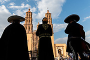Mariachi performers silhouetted in front of the Parroquia Nuestra Señora de Dolores Catholic Church also called the Church of our Lady of Sorrows at the Plaza Principal in Dolores Hidalgo, Guanajuato, Mexico. Miguel Hildago was a parish priest who issued the now world famous Grito - a call to arms for Mexican independence from Spain.