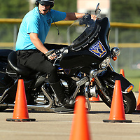Officer Johnson keeps his full attention on the course as he leans his motorcycle in and out of the cones.