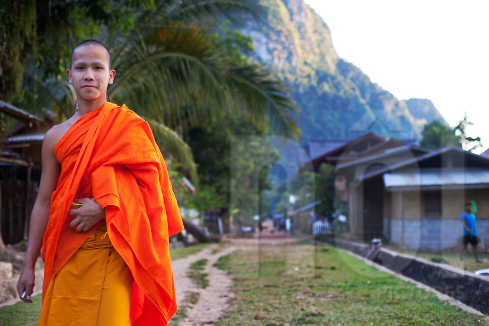 A monk poses in Muang Ngoi, Laos